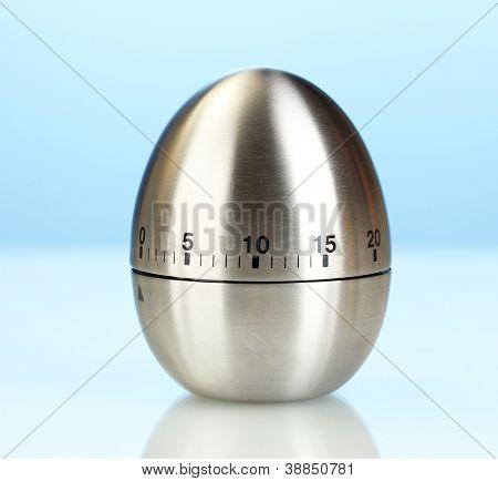 metal kitchen egg timer on a blue background
