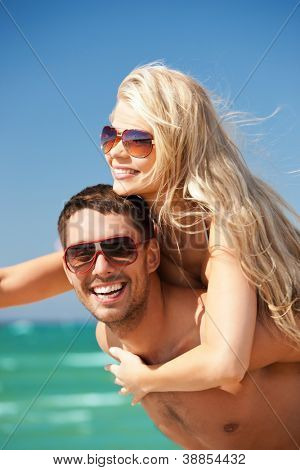picture of happy couple in sunglasses on the beach (focus on man)