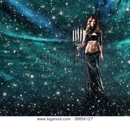 Fashion shoot of beautiful female pilgrim in a long dress over the Christmas background with the snow and stars