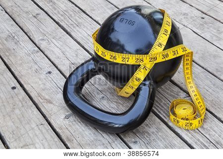 kettlebell and measuring tape on wooden deck - fitness and exercise concept