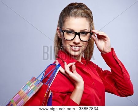 Shopping woman holding bags, isolated on grey studio background.