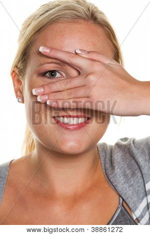 a young woman looking through the fingers of her hand. symbolic photo for clear view and flirt