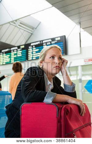 business woman waiting for her departure at the airport. symbolic photo for delays, flight cancellations, strikes