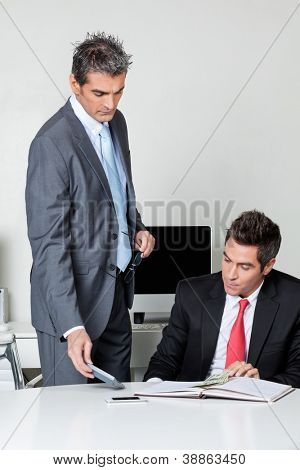 Businessmen calculating finances at desk in office