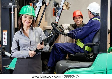 Portrait of smiling female supervisor with foremen communicating at warehouse