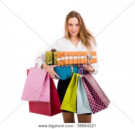 Shopaholic young woman holding gifts and shooping bags on white background