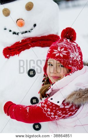 Winter fun, snowman and happy girl making a snowman