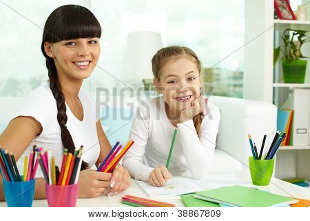 Portrait of lovely girl and her mother looking at camera while drawing with colorful pencils