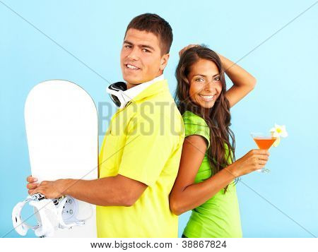 Portrait of happy couple with cocktail and skateboard looking at camera