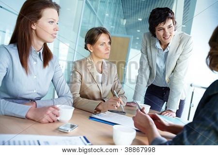 Image of three attentive businesswomen listening to their employer at meeting