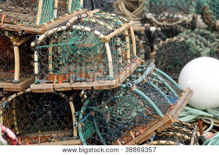 Lobster pots and creels in pile seen in harbor.