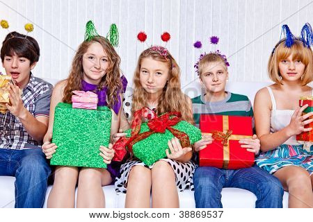 Cheerful teenagers with festive decoration on heads holding presents