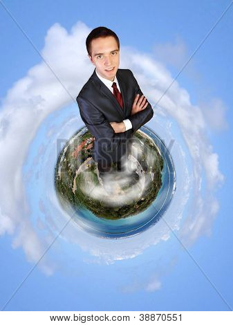 Planet earth against sky background and businessman standing on top of it