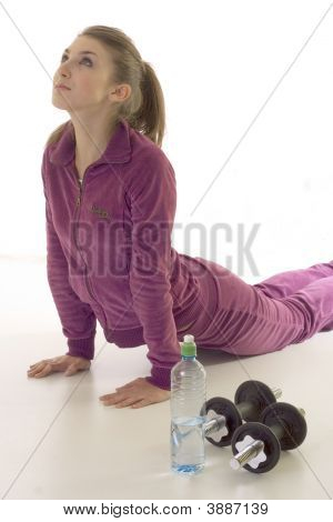 Young Brunette Girl Exercising On The Floor Isolated On The White Background