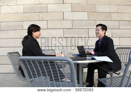 Attractive man and woman Chinese business couple working on laptop computer