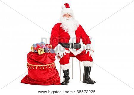 Weihnachtsmann mit Sack voll sitzen präsentiert isolierten auf weißen Hintergrund