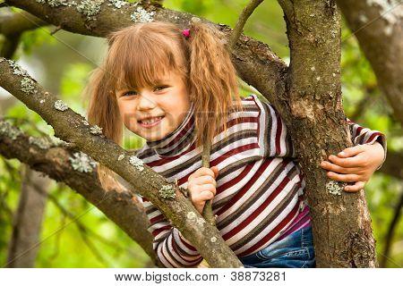 Schöne Mädchen posiert auf einem Baum im Garten sitzen