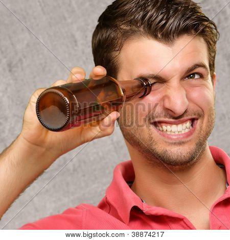 man looking inside an empty bottle, indoor