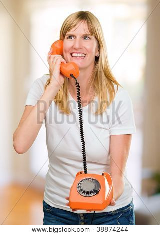 pretty woman talking on telephone against an abstract background