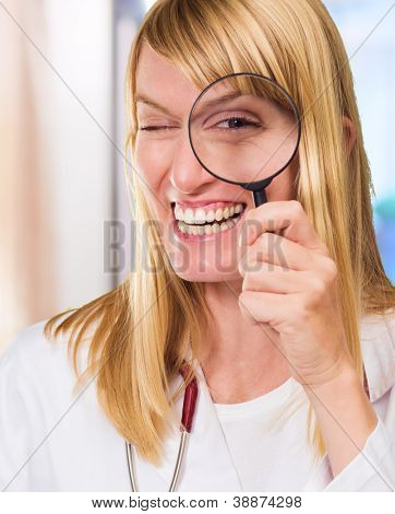 Happy Doctor Looking Through Magnifying Glass against an abstract background