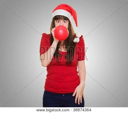 christmas woman blowing a balloon with her eyes crossed against a grey background