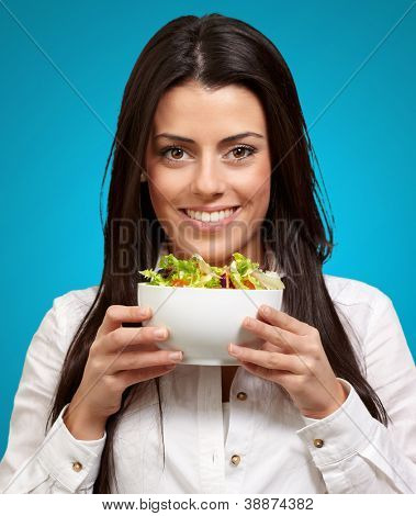 Young Girl Showing A Bowl Of Salad Isolated On blue Background