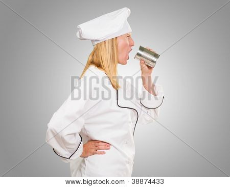 Female Chef Holding Tin Shouting against a grey background