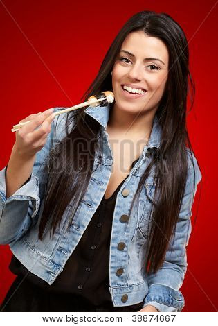 Young Woman Holding A Piece Of Sushi With Chopsticks On Red Background
