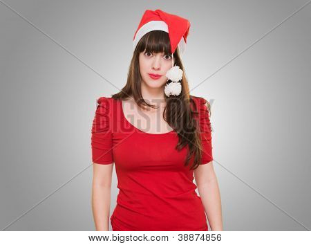 confused woman wearing a christmas hat against a grey background