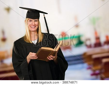 Happy Graduate Woman Holding Book at an assembly hall, indoor