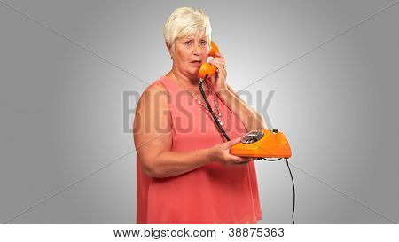 Portrait Of A Senior Woman Holding A Retro Phone On Gray Background