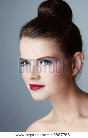 Portrait of young pretty woman looking upwards with curious expression