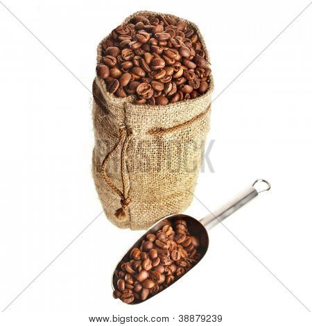 Burlap sack of coffee beans with stainless steel scoop on white background