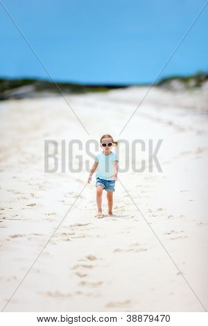 Adorable little girl walking at Caribbean beach