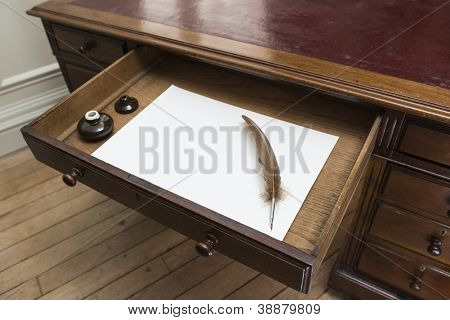 Vintage set with quill and ink pot on top of parchment paper inside writing desk drawer.