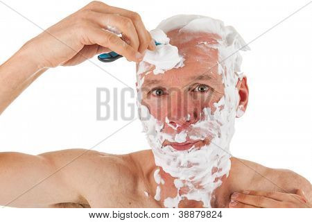 Bald man with razor and foam is shaving his head