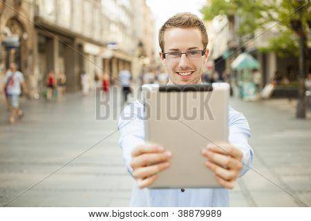 Homem de empresário manter computador tablet no espaço público