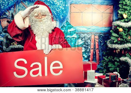 Santa Claus holding sale board over Christmas background.