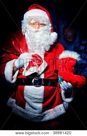 Santa Claus posing with presents over dark background.