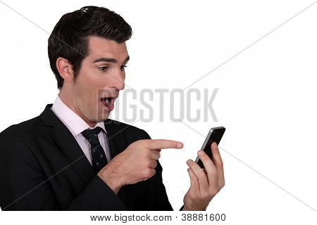 Surprised man pointing to his mobile phone