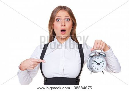 discontented young woman pointing finger at the alarm clock. isolated on white background