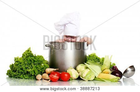 Baby cook looking in pan and vegetables around isolated on a white