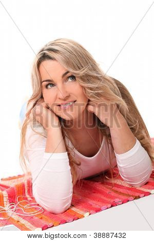 Portrait of attractive middleage woman with adorable smile lying on a mat