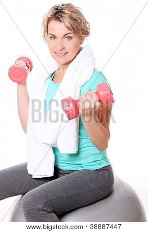 Cute mid aged women with towel do exercises with dumbbells ona a ball