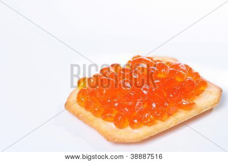 Close up of red tasty caviar on a cracker over a white background