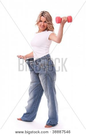 Happy mid aged woman in big pants after weight losing with dumbbell in hand