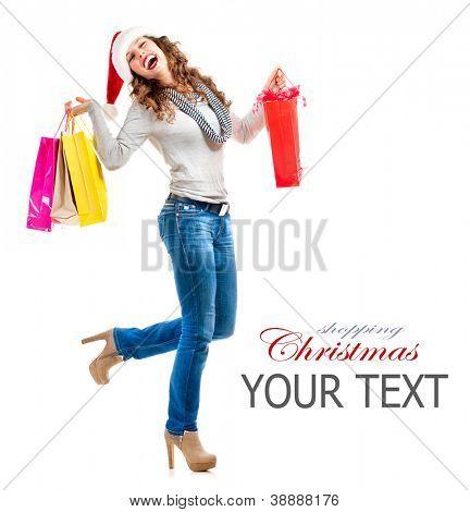 Chica de moda de Santa con bolsas de compras. Compras de Navidad. Ventas. Retrato de cuerpo entero