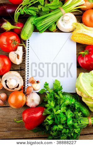 Fresh Organic Vegetables and Spices on a Wooden Background and Paper for Notes.Open Notebook. Diet. Dieting Concept