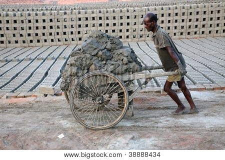 SARBERIA,INDIA, JANUARY 14: Brick field. Laborers are carrying soil from the river and keeping them in the brick field area on January 14, 2009 in Sarberia, West Bengal, India