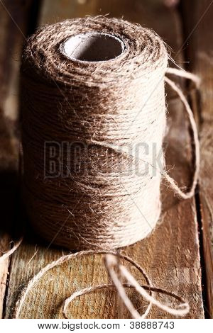 Artistic image of spool of thread over wooden surface